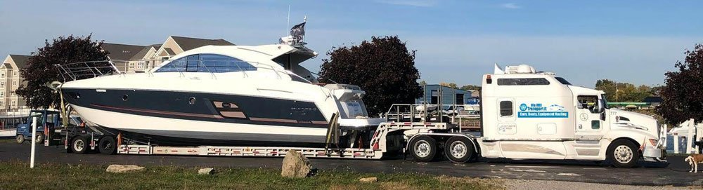 White truck with the We Will Transport It logo hauling a beautiful yacht on trailers