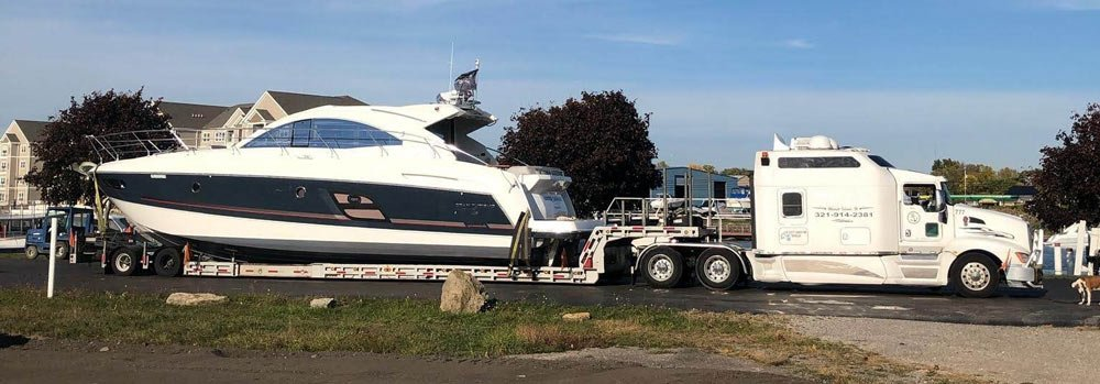 White and blue huge beautiful Yacht being transported for a White truck, Boat Transport Montana