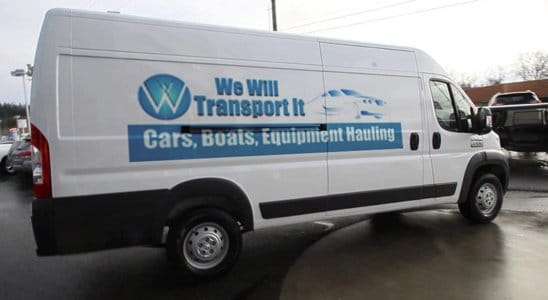 A white Cargo Van with the We Will Transport It logo on it
