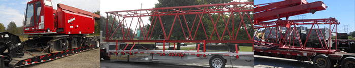 3 red cranes on trucks ready to be tranported