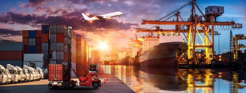 Containers in a Port with an airplane flying over, a ship and the sky reflected in the sea