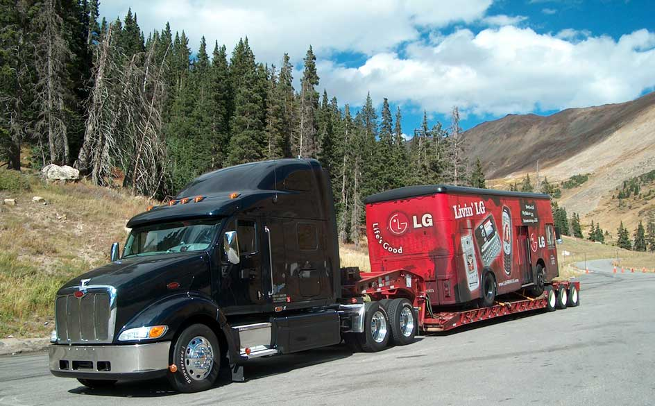 Coca Cola machine is being transport for a black truck
