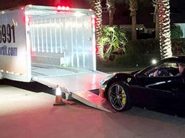 Huge enclosed car transport trailer and a Ferrari car ready to be on the trailer