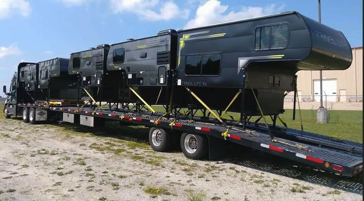 5 RVs on an open trailer being transported for a green truck