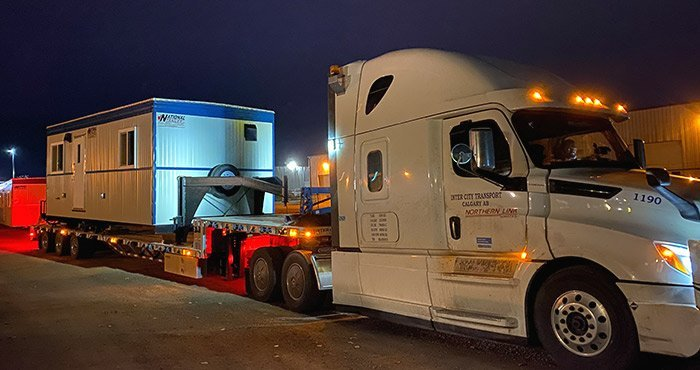 A white truck is transporting a white and blue office trailer