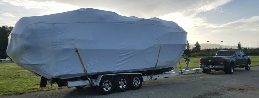 Boat covered with a boat cover and it is being pulling by a Ford F250 Truck